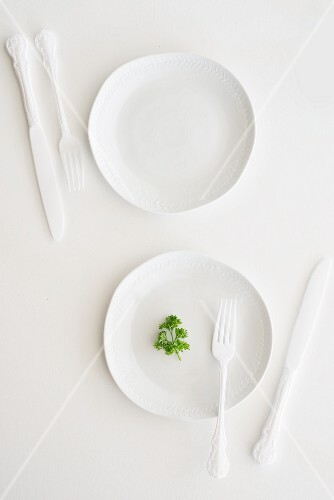 White plates, cutlery and parsley