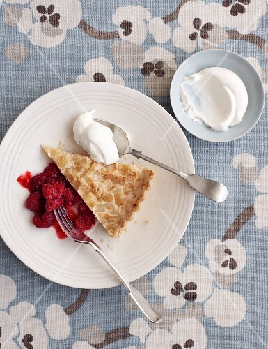 A slice of almond tart with raspberry compote and cream