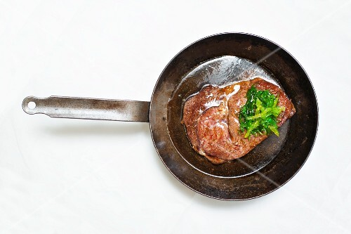 A fried beef steak in a pan (seen from above)
