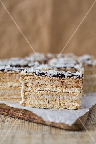 A layered sponge cake with walnut and coconut cream glazed with ganache