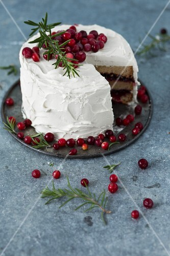 A winter cranberry cake with vanilla frosting and rosemary