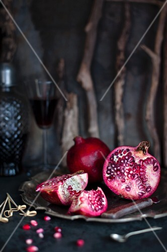 Two pomegranates on a metal plate with pomegranate seeds and juice next to them
