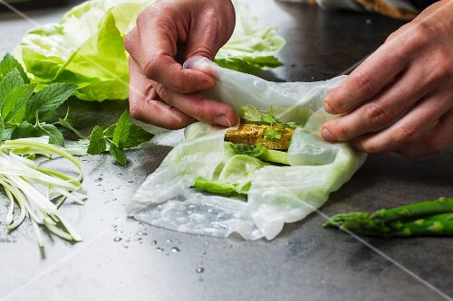 Vegan rice paper rolls with tofu and asparagus being made