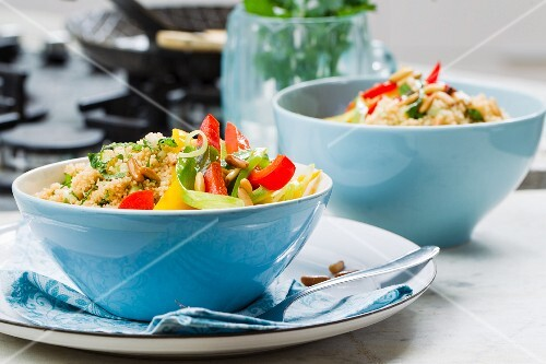 Vegan couscous salad with colourful fried vegetables and parsley