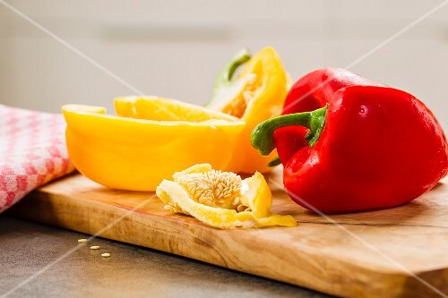Red and yellow peppers on a wooden chopping board
