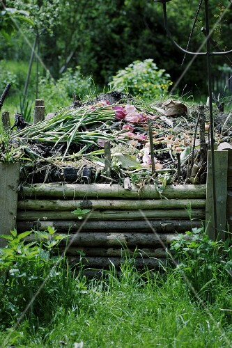A compost heap behind a wooden fence