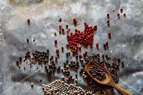Various peppercorns on a tray with a wooden spoon
