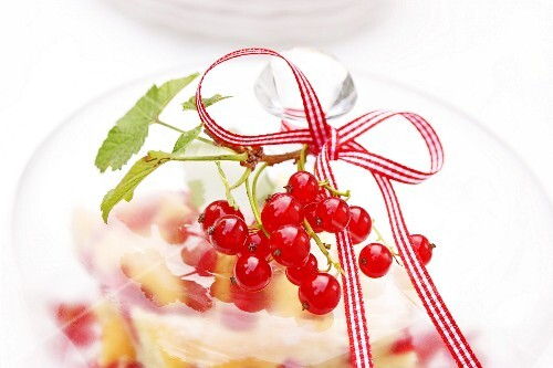 Redcurrants on a glass cloche covering a redcurrant cake (close-up)