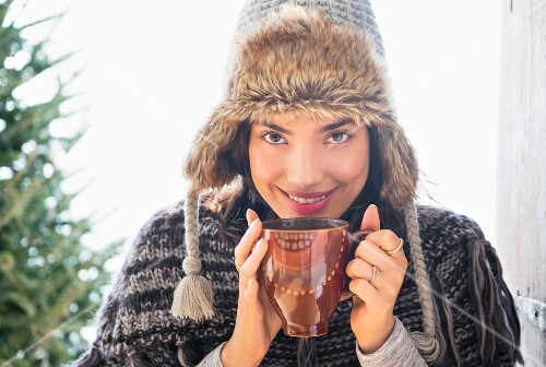 A woman wearing a fur hat holding a cup of coffee