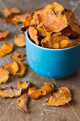 Homemade sweet potato crisps with salt in a blue cup