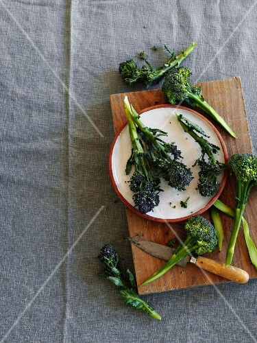 Fresh broccoli on a chopping board and on a plate (seen from above)