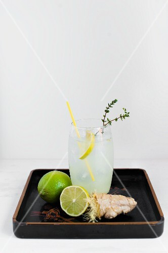 A glass of ginger and lime soda with ingredients on a varnished tray