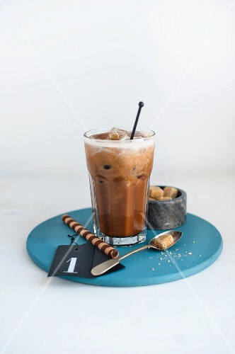 A glass of hazelnut iced coffee, brown sugar cubes and a wafer roll