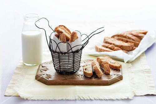 Cantucci in a wire basket and on a chopping board