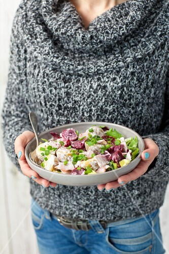 A woman holding a bowl of beetroot and potato salad with ham and a creamy horseradish sauce