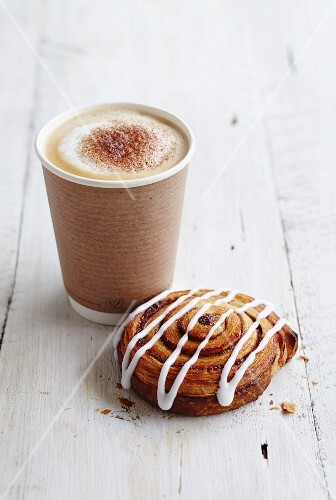 A coffee cup to take away with an iced Danish pastry
