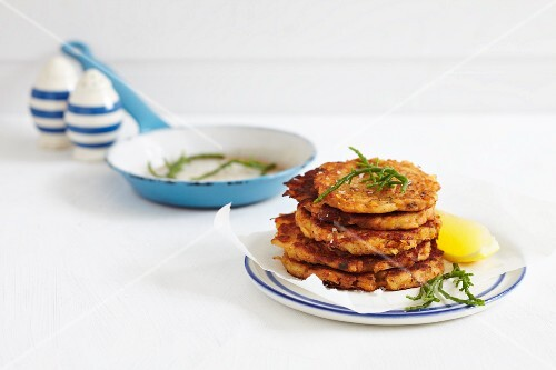 Deep fried fish fritters with a lemon wedge and samphire
