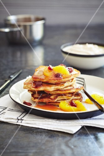 A stack of pancakes with oranges and cranberries