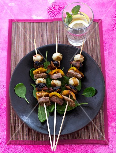 Ox meat skewers with plums and mini mozzarella on a bed of basil leaves