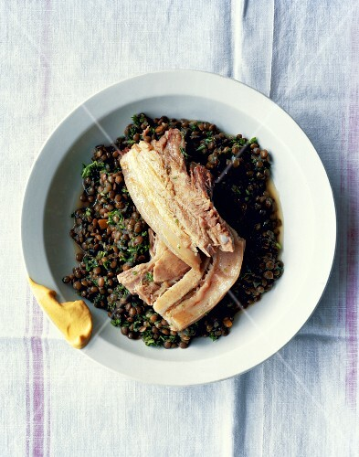 Boiled pork belly on a bed of lentils