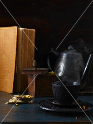 A cup of tea with a teapot on a wooden table