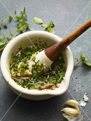 Herb oil with garlic in a mortar