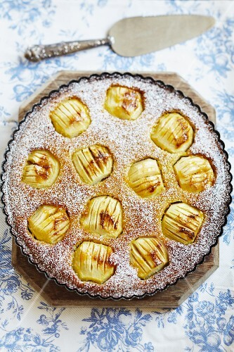 A large apple tart with whole apples and icing sugar
