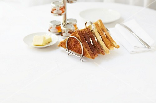Toast in a toast rack served with butter and various jars of jam