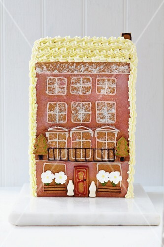 A gingerbread town house with sugar flowers and a balcony