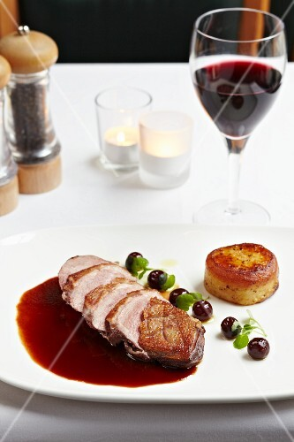 Duck breast in a pool of red wine sauce with cherries and a potato cake