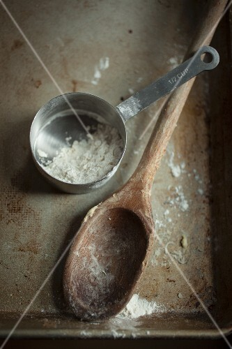 A wooden spoon and a measuring cup with flour on a baking tray