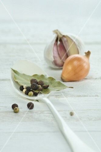 A bay leaf, pepper corns and allspice berries on a spoon with an onion and a bulb of garlic in the background