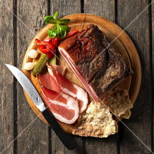 Tyrolean bacon on a board Schüttelbrot (crispy unleavened bread from South Tyrol) with conichons, lamb's lettuce and a knife