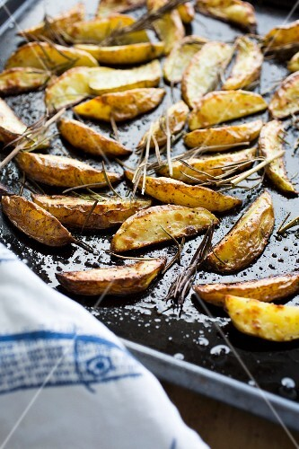 Roasted potato wedges on a baking tray (close-up)