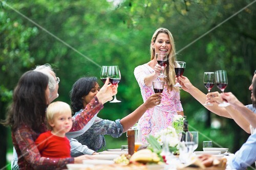 Friends raising glasses of red wine at a garden party