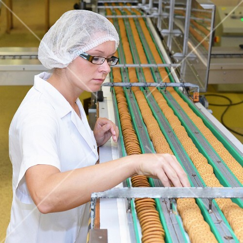 A woman checking biscuits on a conveyor belt in a baking factory