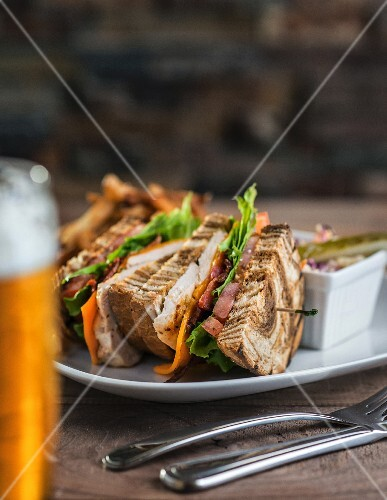 Club sandwich on marble rye bread with a side of coselaw and a beer