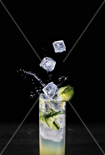 Ice cubes falling into a summer cocktail garnished with cucumber