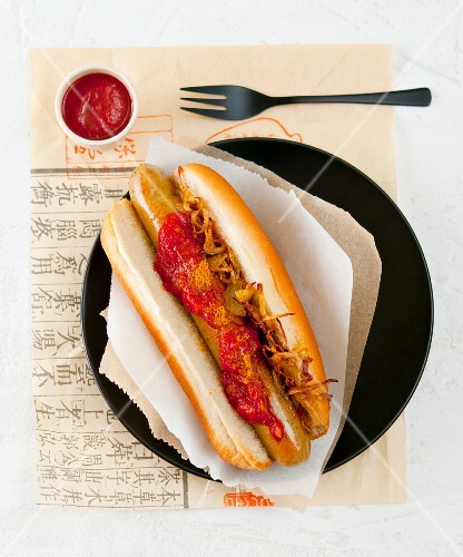 A hot dog with crispy onions and ketchup (Asia)