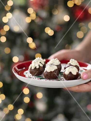 Hands holding a Christmas plate with Christmas pudding truffle pralines
