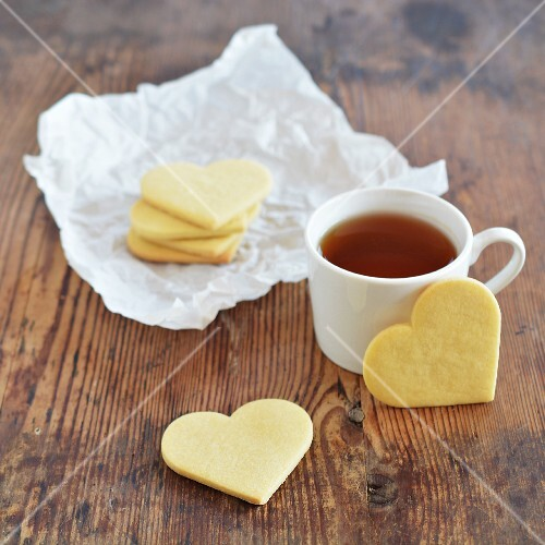 Heart-shaped biscuits with a cup of tea on an old wooden table