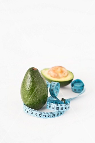 Fresh avocados with a measuring tape