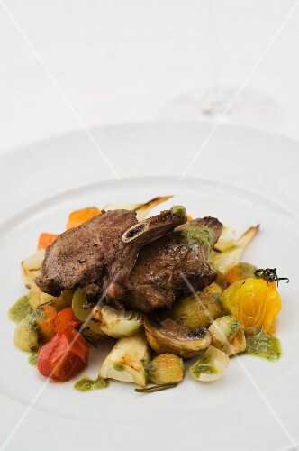 Wild boar chops on root vegetables, mushrooms and onions