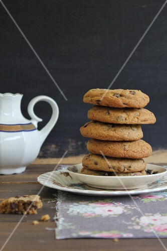 A stack of chocolate chip cookies and a pot of tea