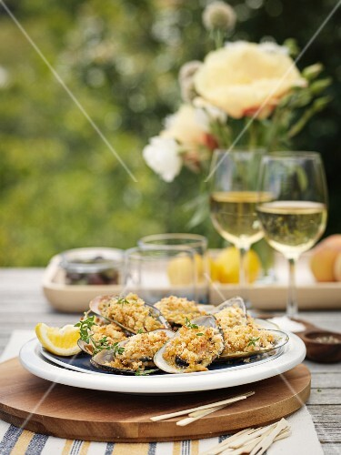Gratinated oysters and white wine on a garden table