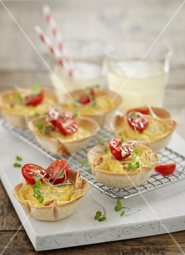 Scrambled eggs with diced ham in pastry cups garnished with tomatoes and cress
