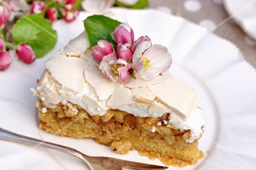 A slice of apple cake topped with meringue and flowers on a plate