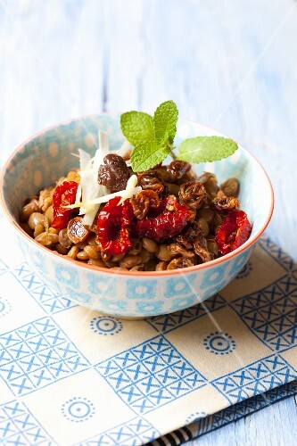 Lentil salad with onions, dried tomatoes, raisins, olives and mint