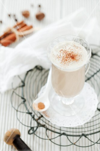 A glass of chai tea latte on a wire rack with whole spices