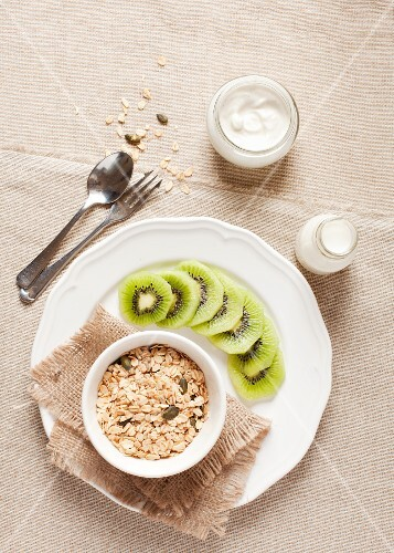 A healthy breakfast of oats, pumpkin seeds, milk, yoghurt and kiwis